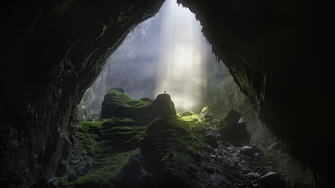 Shaft of light beaming down into Son Doong, the worlds largest cave. Photo by Shutterstock/David A Knight.