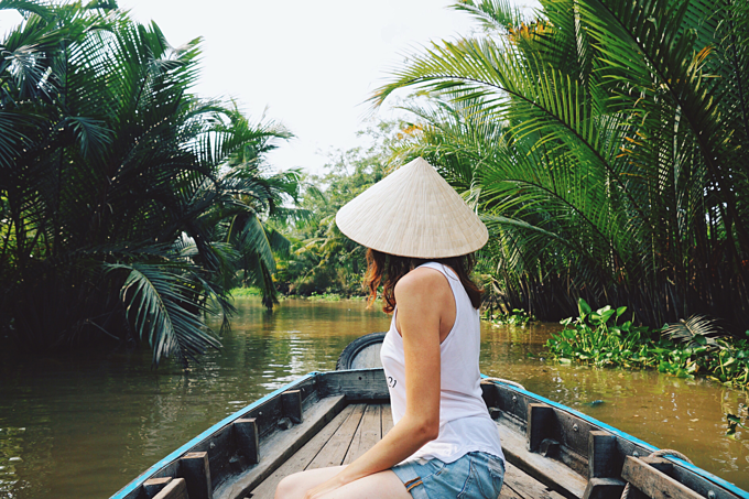 A young woman in a Vietnamese traditional hat rides a boat on the Mekong River in Vietnam. Photo by Shutterstock/Bucha Natallia.