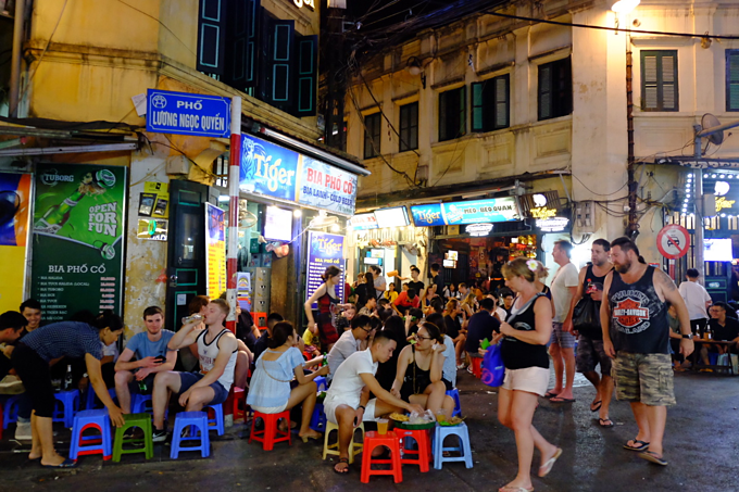 Foreign tourists enjoy beer and food at the intersection of Hanois Ta Hien and Luong Ngoc Quyen streets. Photo by VnExpress/Giang Huy
