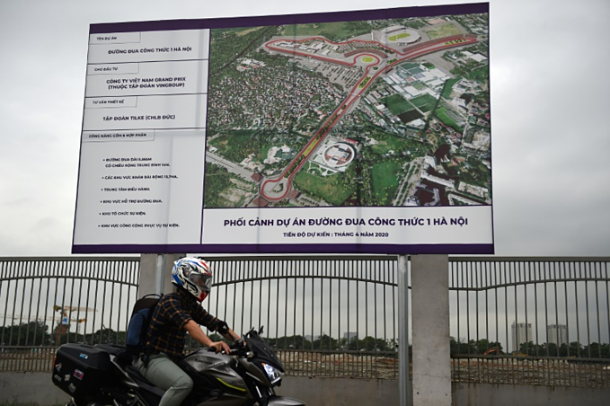 A map rides past a blue print of Hanois planned F1 race track. Photo by AFP/Nhac Nguyen