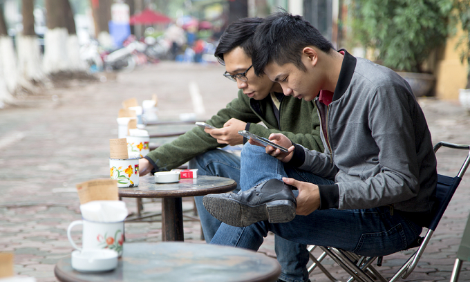 In coffee stores, the number of people glued to their smartphones far outnumbers those reading books. Photo by Shutterstock/Asia Images