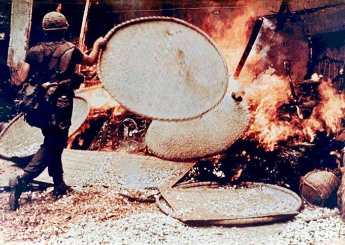 An American soldier throws bamboo sieves into the fire of burning houses during the My Lai massacre on March 16, 1968. Photo courtesy of Ronald L.Haeberle