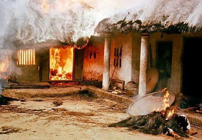 A house burns in My Lai village on March 16, 1968. A corpse burns outside the house. Photo courtesy of Ronald L. Haeberle.