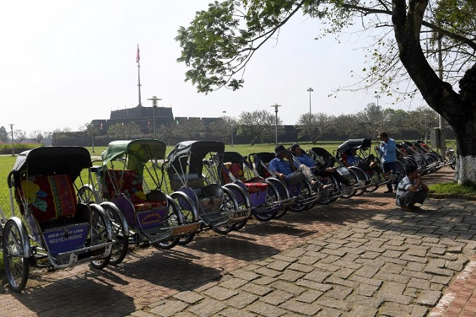 Cyclo drivers wait for tourists at the site of the former imperial citadel in Hue, central Vietnam. Photo by AFP/Hoang Dinh Nam