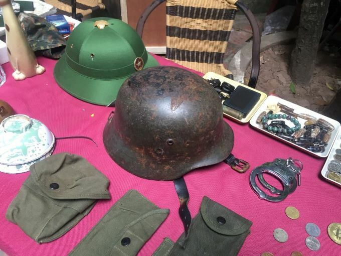 The iron cap used in the World War II (middle) is offered at VND6 million ($260) at the market. Photo by VnExpress/Minh Huong.