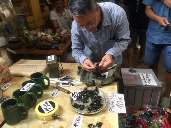 A customer selects stockpile Russian plugs, produced between 60s and 70s. Still in good use, the plug is one of the best selling in Minh Quang's booth. Photo by VnExpress/Minh Huong.