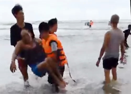 A video screenshot shows a man who drowned in La Gi beach, Binh Thuan, is carried to shore on August 10, 2019.