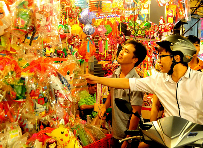 A man inspects lantern products on Luong Nhu Hoc Street, known as the busiest lantern market in HCMC in the lead up to the Mid-Autumn Festival. Photo acquired by VnExpress.