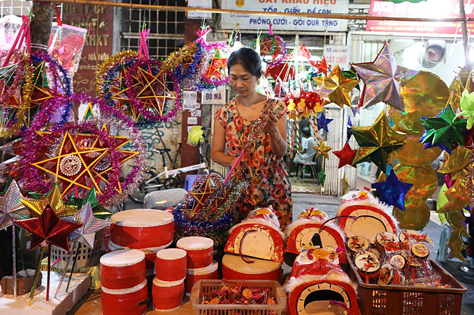 A woman sells traditional toys such as star-shaped lanterns, paper masks, small drums, and lion heads on Hang Ma Street. Made-in-Vietnam toys dominate the market this year, a trend that has overtaken the sale of imported Chinese products which could be seen in previous years.