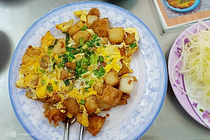 Dat Thanh stall opens at 4 pm every day at 5 pm and it's rarely ever empty. The crispy dish is made with rice flour cakes chopped into chunky squares and fried on a large flat pan before being topped with whipped eggs and chopped spring onions. You can find the stall near Ban Co market at 277 Vo Tan Street Street for this VND26,000 per serving dish ($1.1). Photo by VnExpress/Di Vy
