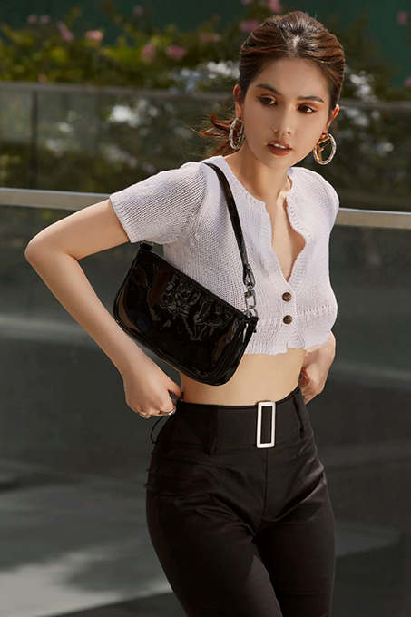 Model Ngoc Trinh wears a crop top with a shoulder bag and oversized hoop earrings, typical items of the '90s fashion trends.