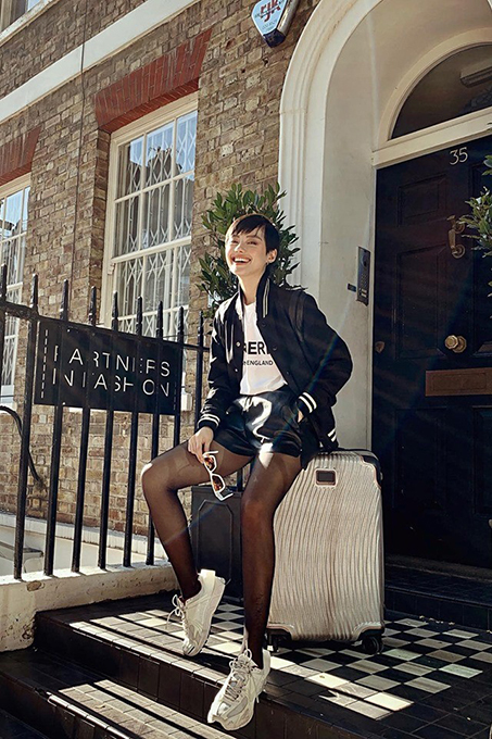 Model Khanh Linh embraces the 90s style with leather shorts and a baseball jacket.