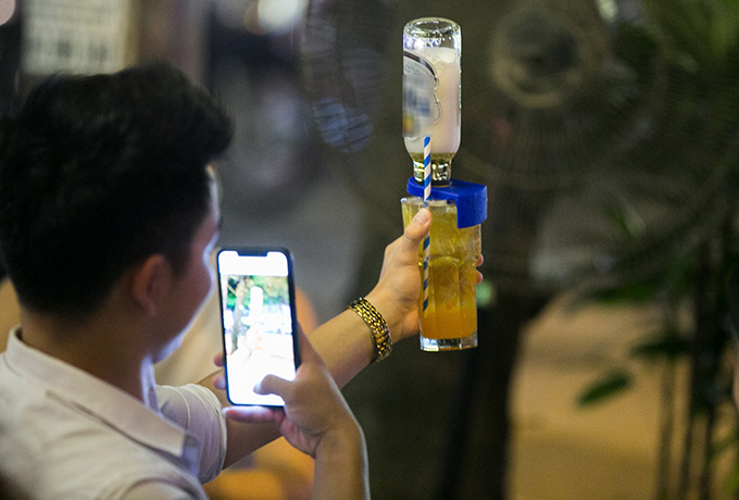 A customer takes a photo of his beer cocktail. Photo by VnExpress/Tung Dinh.