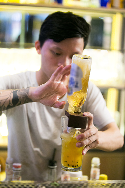 A bartender sticks a beer bottle in a passion fruit mojito. Photo by VnExpress/Tunh Dinh.