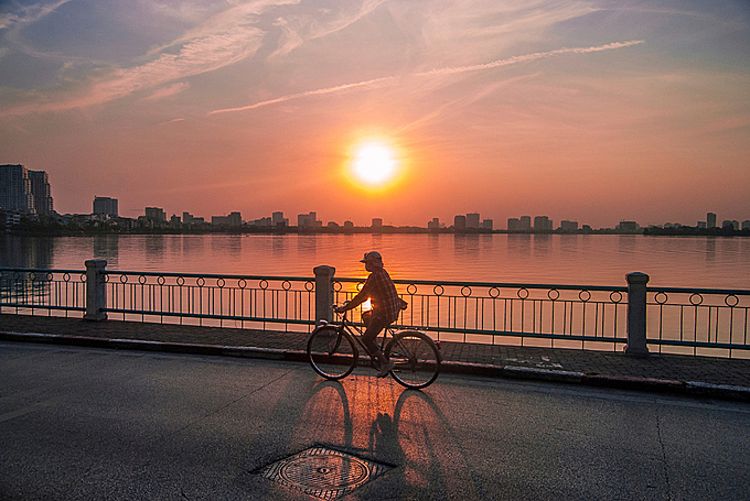 A woman riding a bicycle in Hanoi sunset. Photo by Shuttlestock/Raphael Rivest.