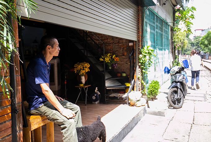 Nguyen Le Quan sit in front of his house, looking out to the Hanoi Train Street. Photo by VnExpress/Tung Dinh.