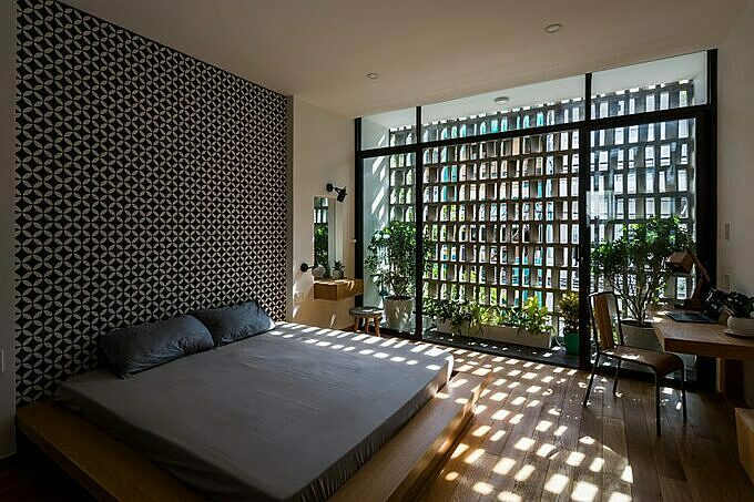 The bedroom is filled with sunlight through the brick facade.