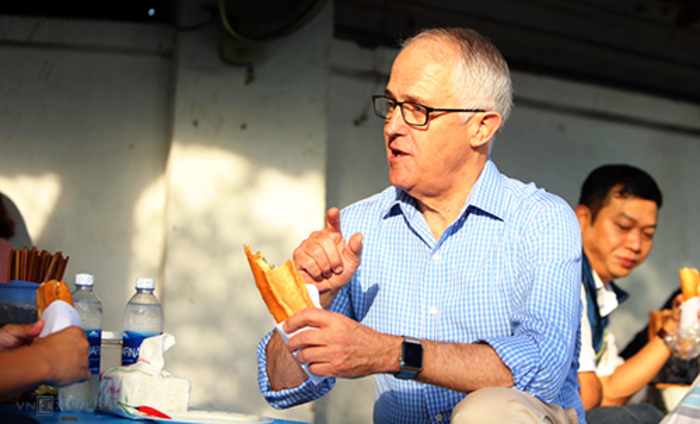 Turnbull ate the banh mi sitting on a sidewalk stool. Photo by VnExpress/Dac Thanh.