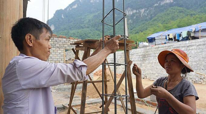 After finishing their stilt house, a couple erects one of the steel poles needed for the construction of their kitchen and bathroom.