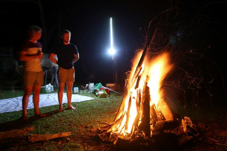 Campers standnext to a bonfire after finishing the tour.The tourists campin the love valley next to a small stream inCo Da Village, enjoying fresh air and quietude they can hardly find in the cities.