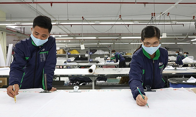 Designers draw details and sizeof masks on antibacterial cloth before feeding it into a cutting machine. Photo by VnExpress/Ngoc Thanh.