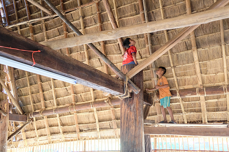 The roof is covered with 20-cm-thick-layers of grass. Large wooden pillars also become a place for children to play.