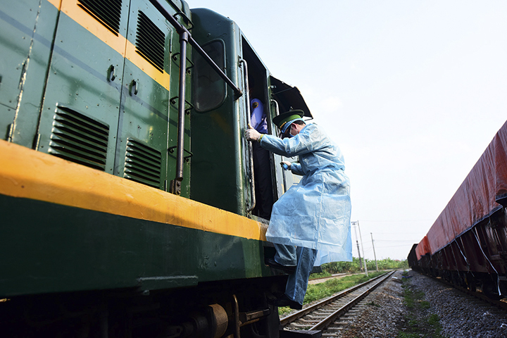 As a train nears the Vietnam border from the Chinese side, Tran Van Huong of the Lao Cai International Border checkpoint hops on to carry out entry procedures. His task is to inspect the ID of those on the train to make sure no one is entering Vietnam illegally.