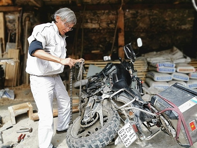 Hung repairs his motorbike during his trip in....Photo courtesy of Tran Le Hung.