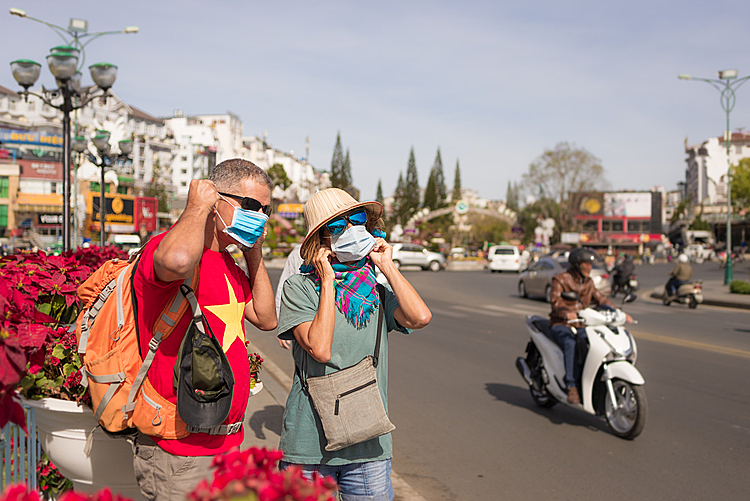 Two foreign tourists wear masks as they explore downtown Da Lat . Photo by Shutterstock/Fabio Lamanna.