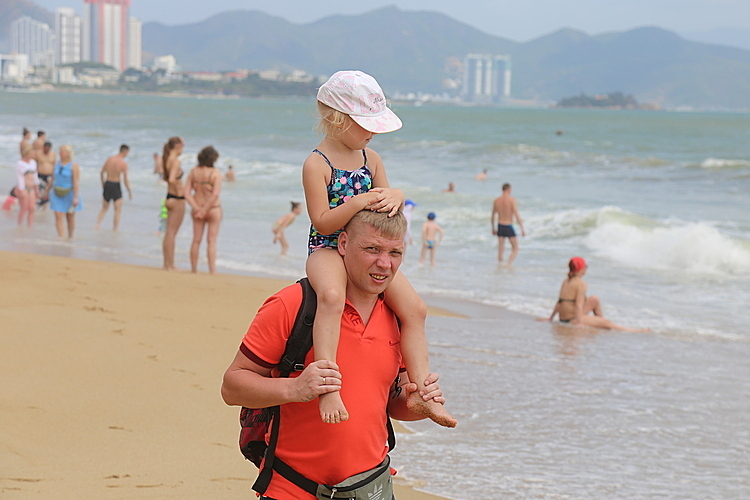 Tourists walk on the beach in the central province of Nha Trang on February 20. Photo by VnExpress/Xuan Ngoc.