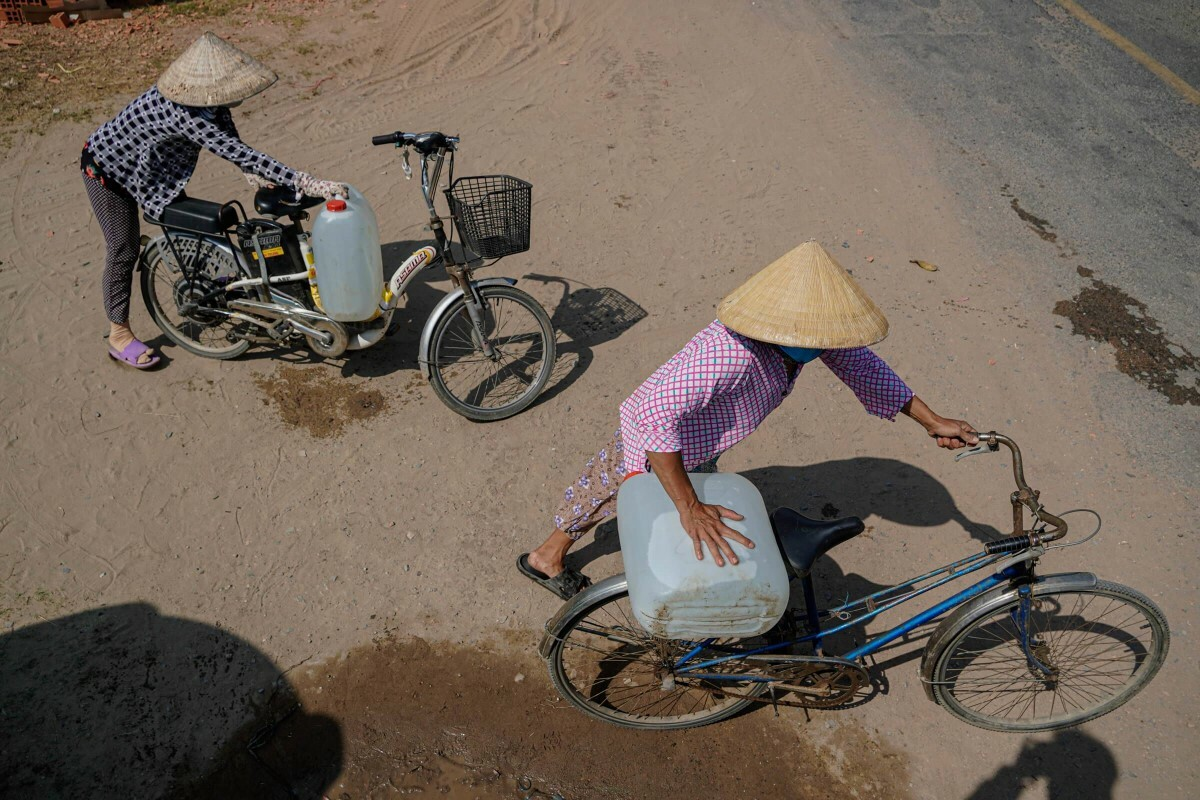 Two women carry water bottles on their bikes.Drought and salinization in the Mekong Delta this year is especially tough, even breaking previous records in 2016. About 40,000 hectares of paddy for the winter-spring period in the Delta have been damaged, and about 95,000 families in the Delta now lack freshwater for daily activities. Five Mekong Delta provinces: Long An, Tien Giang, Ben Tre, Kien Giang and Ca Mau have declared emergency drought states earlier this month.Severe drought and sainization would continue to last until April, experts predicted.