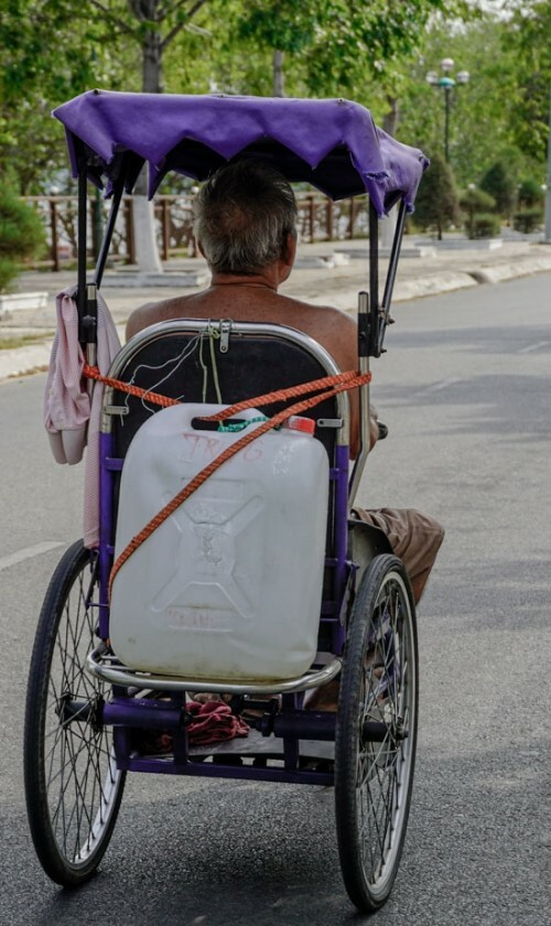 Tran Van Vinh, 74, uses a wheelchair to carry a water can back home, about 1.5 kilometers away. Vinh, part of a family of five, had a stroke years ago. His daughter-in-law lost an arm in a work accident, while his son works as a manual worker and his wife cooks for a local pagoda. Vinh often stays home with his 1-year-old grandchild.