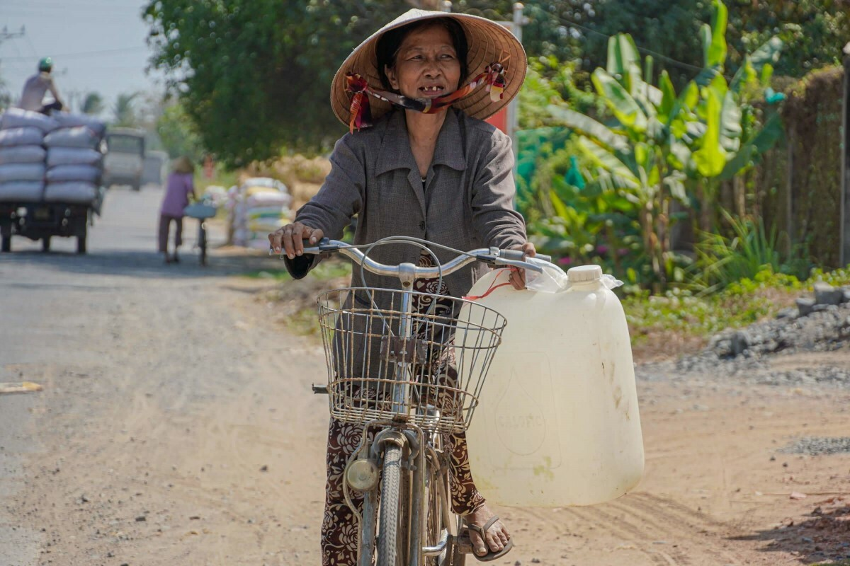 Nguyen Bach Tuyet, 67, in Tien Giang Province, about 40 km from ben Tre, rides a bike for half a kilometer to bring freshwater back to her home.She lives alone in Vinh Huu Commune, Go Cong Tay District; her son works far from home. She has ridden her bike to collect freshwater for nearly two months now.Im old so my limbs are weak, I can only do one ride each day. I use water sparingly, but since I use it for bathing, washing and cooking, it always runs out at the end of the day. I just wish for the rain to come so people dont have to suffer so much, she said.