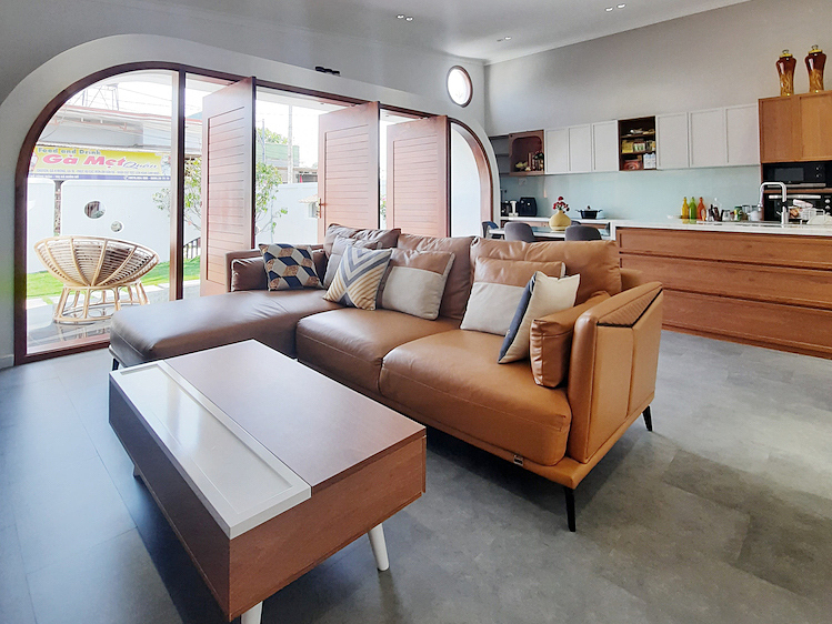 The kitchen and living room share a common space. A large facade door allows natural light and wind to penetrate.