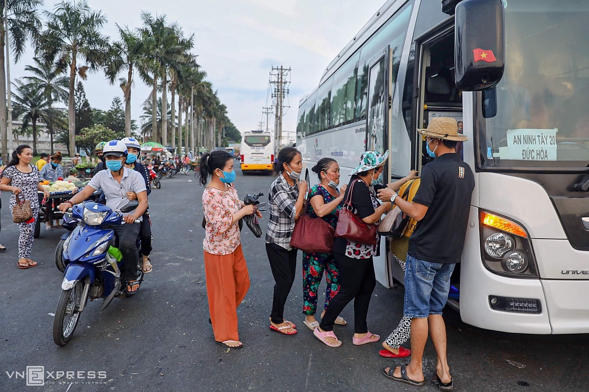 To avoid prolonged congestion in front of the company, some workers in Duc Hoa District in Long An Province hurriedly get on the bus waiting outside.
