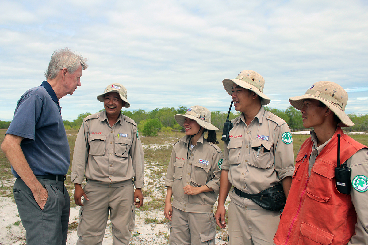 Chuck Searcy (L) talks with a group of Project RENEW peronnel. Photo by VnExpress/Ngo Xuan Hien.