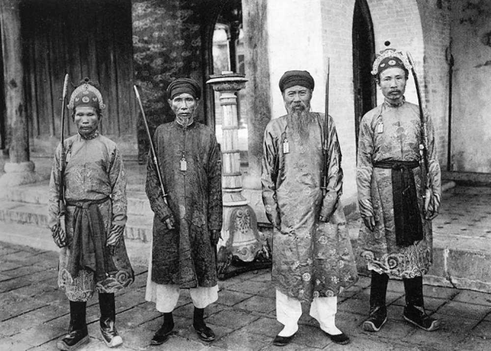 Four court officials in the Hue Imperial Citadel. The ao dai of the Nguyen dynasty in the 19th century had patterns and designs that were strictly regulated under the management of the Ministry of Le. The shirt is embroidered, woven with phoenix, bat, sun, gourd, bowl of buu, five colors ... inside with silk lining.