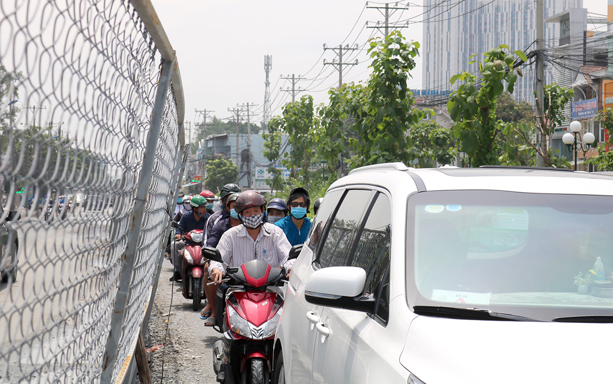 A line of traffic congestion next to a barrier covering a construction site on Tran Nao Street of District 2.