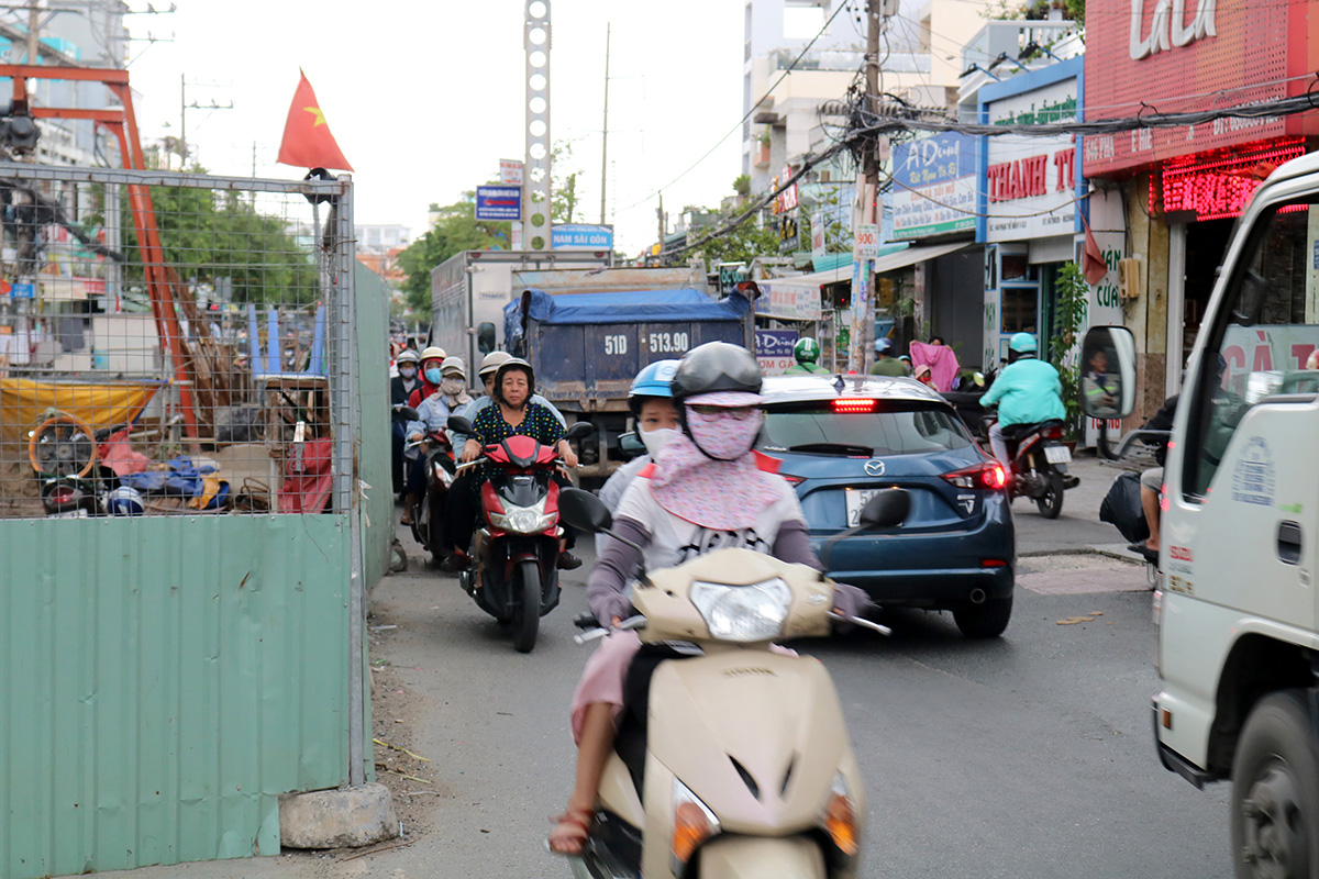 Motorbikes and autos pass by a construction site on Pham The Hien Street in District 8.