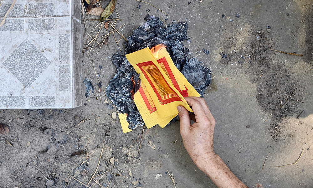Burning hell notes for the dead. Photo by Shutterstock/Zay Nyi Nyi.