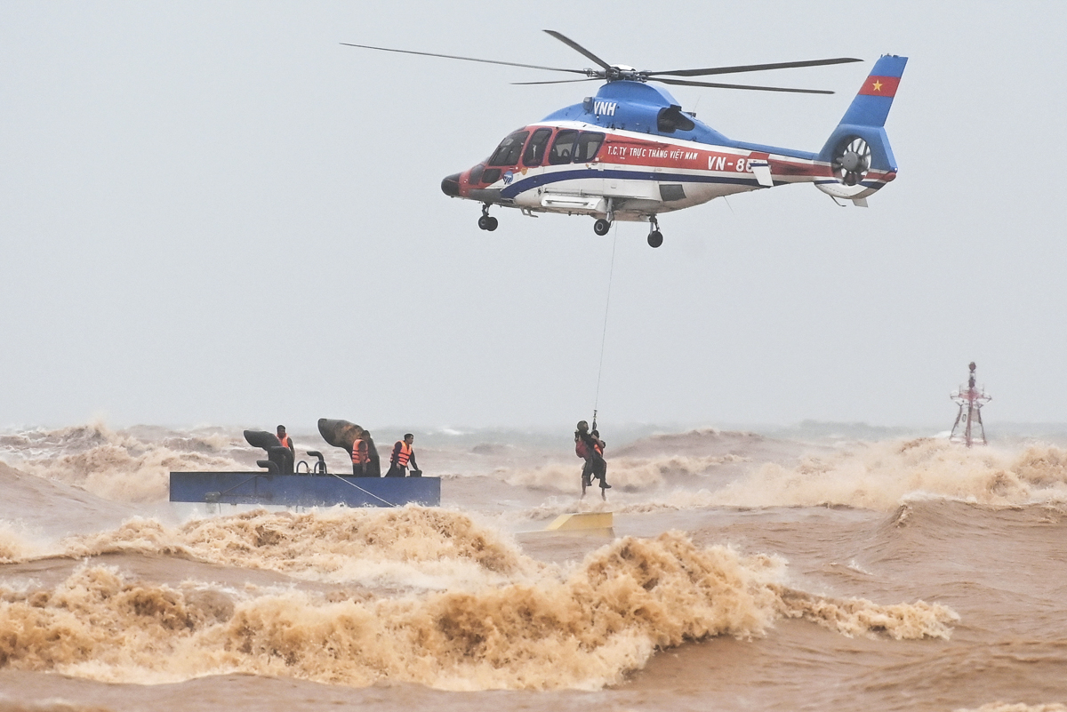 The remaining six men were rescued by a military helicopter. The helicopter flew to the area, sending down a lifeguard to take those men up. The lifeguard has to struggle with the strong winds to reach the cabin every time he drops himself. By the time this rescue mission took place, storm Linfa formed by a tropical depression is heading straight to the central region of Vietnam. The storm has made landfall late Sunday morning in Quang Nam and Quang Ngai Province.