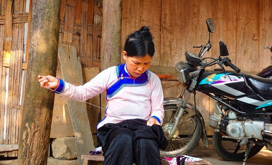 A Giay ethnic woman stitching clothes, Lao Cai Province. Photo by Xu Kien.