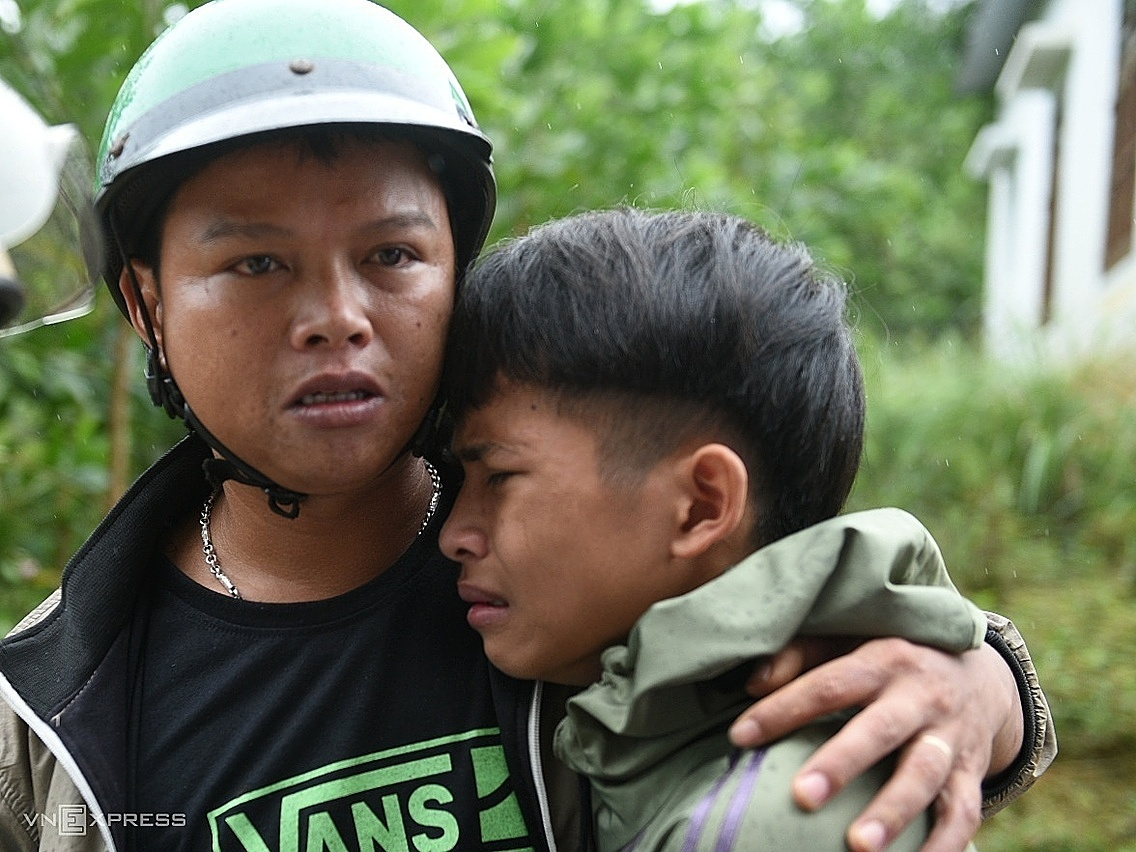 Le Thanh Tu (L) could not stop crying on his teachers shoulder. Photo by VnExpress/Thanh Hue.