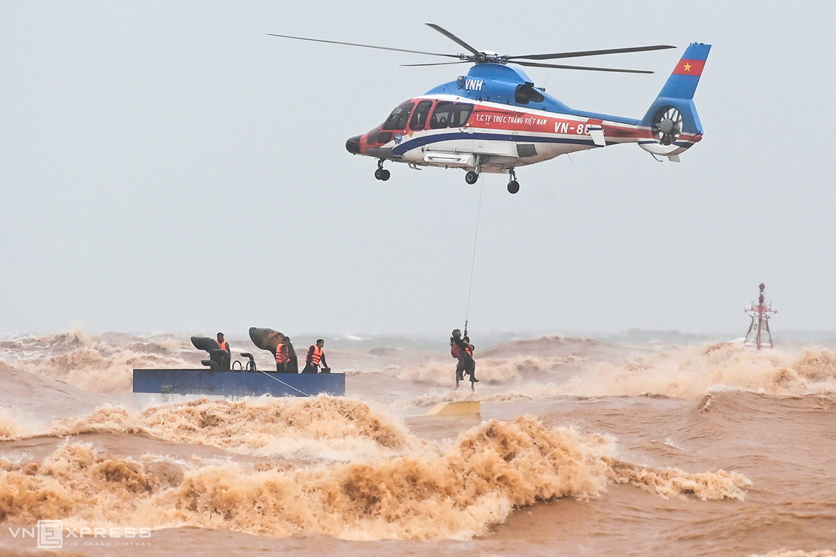 A military helicopter and its crew brave strong winds and rough seas as they lift crew members of Vietship 01 up from the shipAs the rescue mission took place, storm Linfa was heading straight to the central region. Photo by VnExpress/Giang Huy
