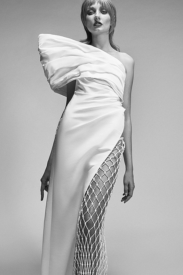 An asymmetrical gown with partial netting and an extra-large shoulder puff.