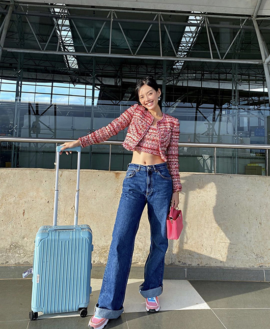 Model Khanh Linh dons a tweed crop top and blazer with wide-leg jeans to show off her abs.