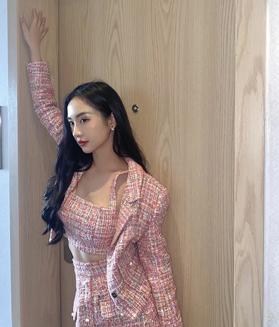 Model Jun Vu goes for pink with a crop top, blazer and skirt made of tweed fabric. The tightly woven wool from the outfits keeps the wearer warm amid autumn days.