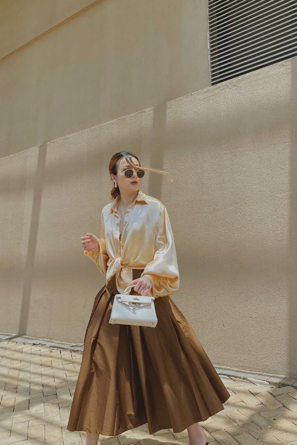 Singer Yen Nhi goes for a classy look with a silk shirt and a circle skirt in beige and brown. Photo courtesy of Yen Nhi.