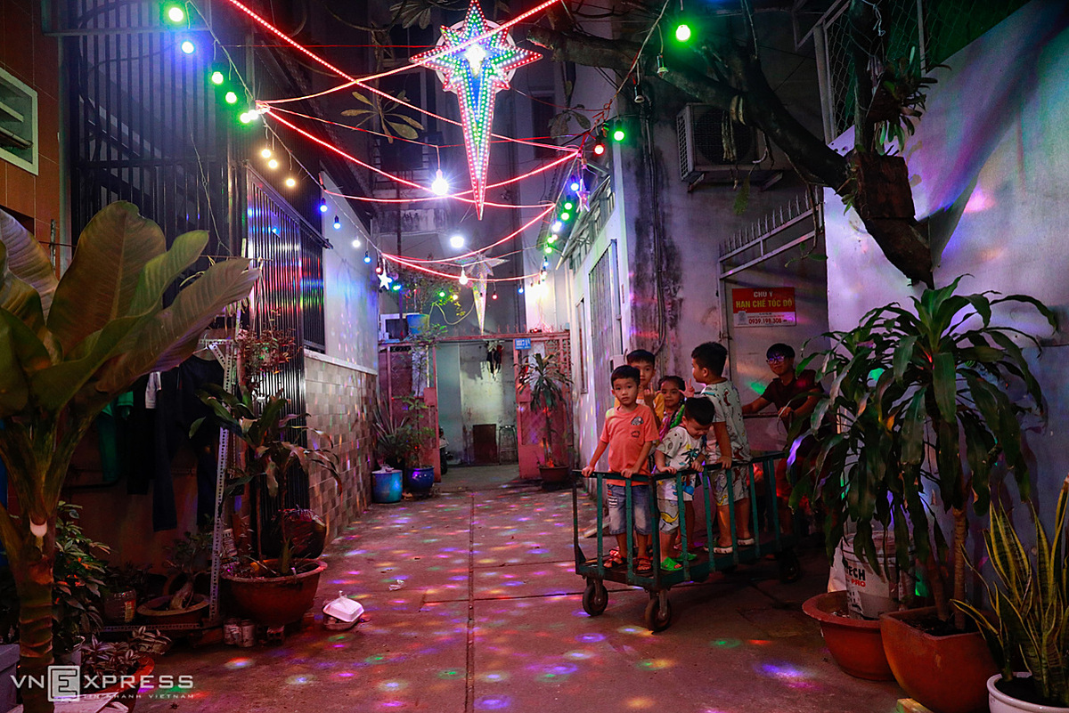 Children are pushed by relatives on a tricycle to roam in an alley on Pham The Hien Street in District 8, which has been lit up by sparking lights and colorful decorations. Days before Christmas, the alleys on this street are more vibrant and bustling than usual. This is also one of the largest Christian communities in Ho Chi Minh City.