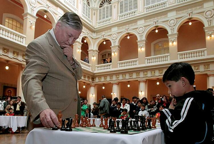 Russian chess grandmaster and former world champion Anatoly Karpov (L) takes part in simultaneous chess games with Hanry Arauz, 6, at the presidential palace in La Paz, June 23, 2010. Photo by Reuters/David Mercado.